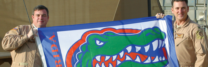 men in uniform hold gator flag